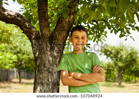 Happy smiling boy leaning against an apple tree in an orchard