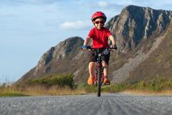 Happy smiling boy riding a bicycle. Andoya, Norway. Summer shot