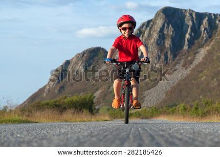 Happy smiling boy riding a bicycle. Andoya, Norway. Summer shot #282185426