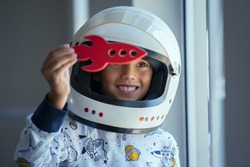 Happy smiling boy wearing an astronaut helmet costume and playing with a spaceship. Child playing with toy rocket near the window. Kid playing with red toy spaceship and dreaming outer space.