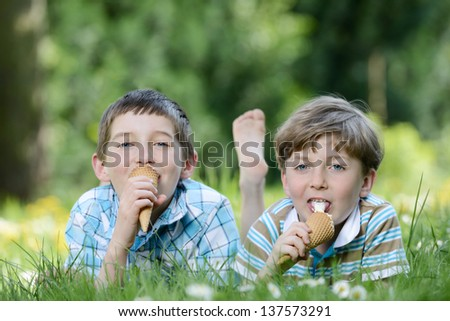 Happy smiling boys eat ice cream on a grass outdoors in spring park