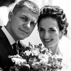 Happy smiling bride and groom posin with wedding bouquet closeup b&w