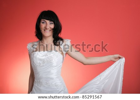 Happy smiling bride in studio on red background