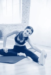 Happy smiling brunette lovely girl on indoors workout. Stretching for calf and back of thigh muscle, warming down exercise. Weight lossing and sporting. Black and white monochrome blue tone picture.