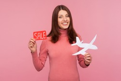Happy smiling brunette woman in pink sweater holding in hands paper plane and sale sign, looking for lowcost airlines, advance ticket booking. Indoor studio shot isolated on pink background