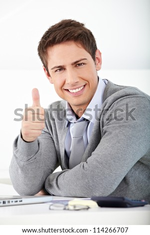 Happy smiling business man holding his thumbs up