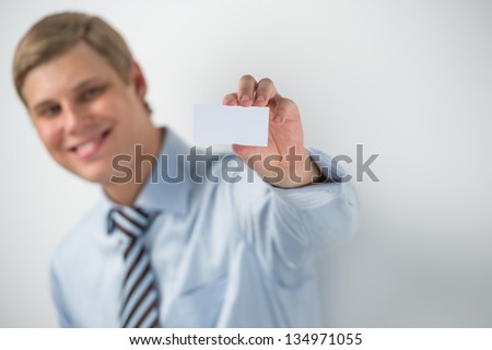 Happy smiling business man showing blank businesscard and dreaming, while leaning on wall at office