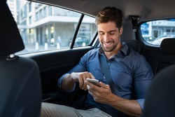 Happy smiling business man typing message on phone while sitting in a taxi. Young businessman in formal clothing using smartphone while sitting on back seat in car. Cheerful guy messaging with cell.