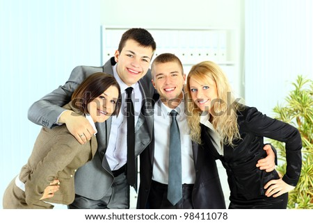 Happy smiling business team of young businessman and businesswoman in office