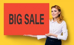 Happy smiling business woman in white confident clothing showing red banner signboard with big sale sign. Advertising studio concept. Blond girl holding paper broadsheet over yellow background, advert