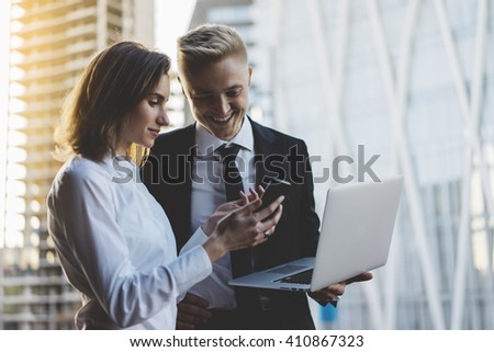 Happy smiling businessman and businesswoman using laptop and smartphone while working on new project, two young professional employers working on portable computer discussing project of constructions