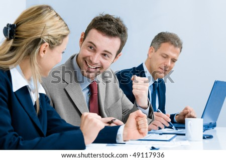 Happy smiling businessman cheering at new success with his business team at office