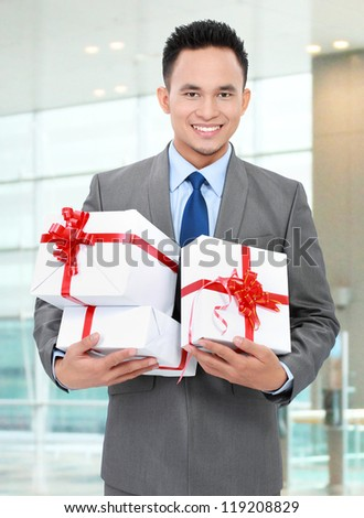 Happy smiling businessman holding gift boxes in the office