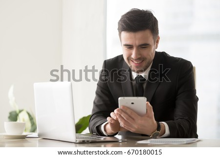 Happy smiling businessman using electronic devices at workplace for digital business management and communication, sitting at office desk in front of laptop, holds tablet, easy apps, banking online