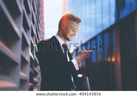 Happy smiling businessman wearing black suit and using modern smartphone near office at early morning, successful employer to make a deal while standing near skyscraper office at night, flare light