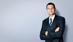 Happy smiling businessman with crossed arms pose, with blank copyspace area for text or slogan, against grey background