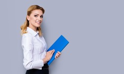 Happy smiling businesswoman holding blue folder, with copy space area for some slogan or text. Confident blond woman in white shirt, isolated over grey color background. Success in business concept.