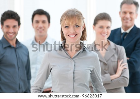 Happy smiling businesswoman standing with her colleagues at modern office