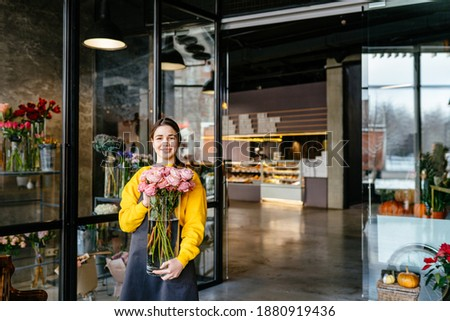 Happy smiling busineswoman girl florist holding vase, will do making bouquet of roses in flower shop for customer. Creative occupation in floral boutique. Floristics, business, decoration concept.
