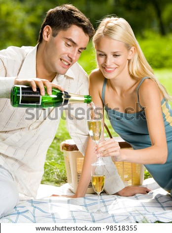 Happy smiling cheerful attractive young couple with champagne at picnic, outdoor - stock photo