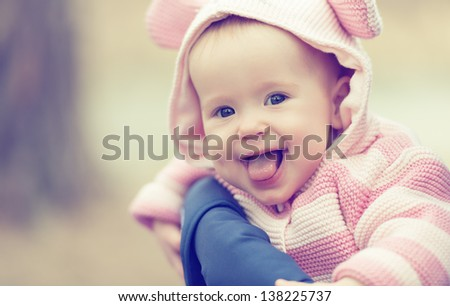 Stock Photo happy smiling cheerful baby girl in pink hood with ears