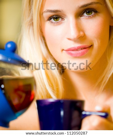 Happy smiling cheerful blond girl with teapot and cup, at home
