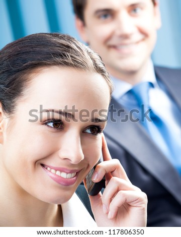 Happy smiling cheerful young business woman with cellphone at office