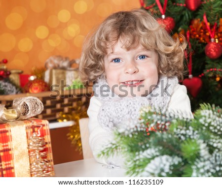 Happy smiling child against Christmas tree with decorations