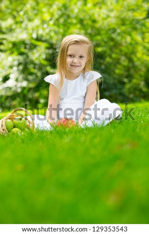 Happy smiling child eating apple  in  park