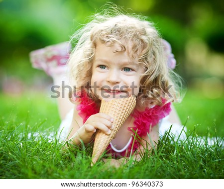 Happy smiling child eating ice-cream on green grass outdoors in spring park