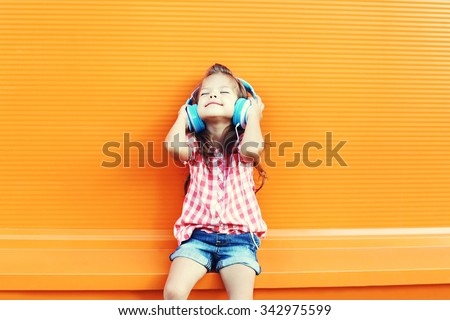 Happy smiling child enjoys listens to music in headphones over orange background #342975599