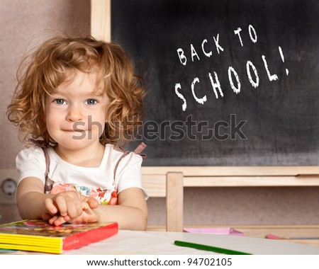 "Happy smiling child in a class against blackboard with text ""Back to school!"""