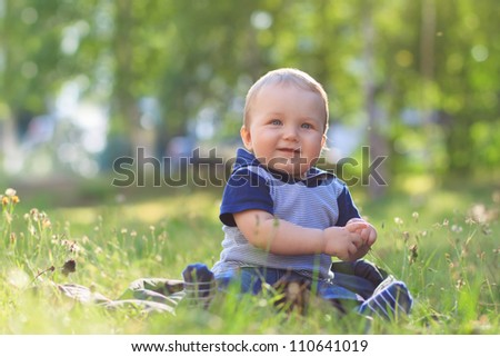 Happy smiling child sitting outdoors in summer park