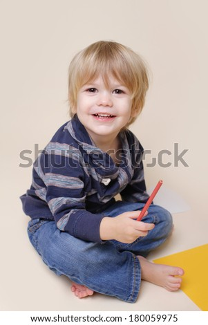 Happy smiling child, with pencil or crayon drawing doing arts