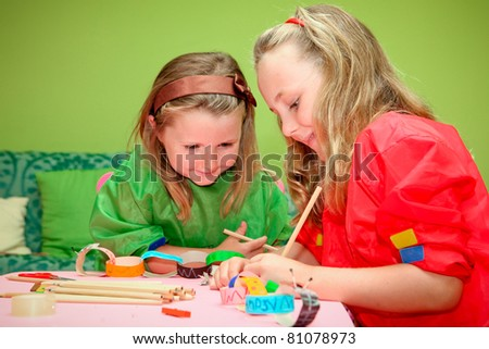 happy smiling children playing drawing and making craft in class at kindergarden school