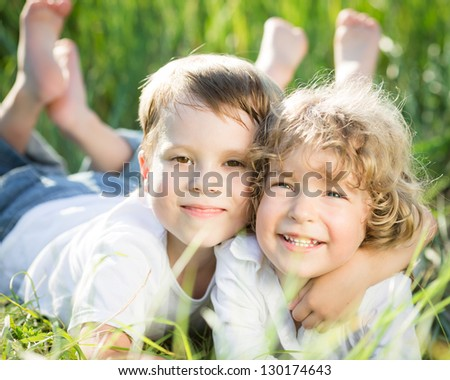 Happy smiling children playing outdoors in spring grass