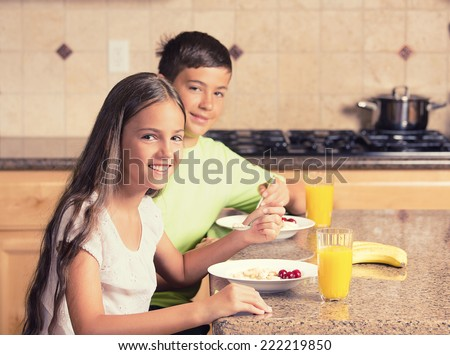 happy smiling children teenager girl and boy, siblings eating cereal with milk and drinking orange juice for breakfast in the kitchen. Positive face expressions, emotions