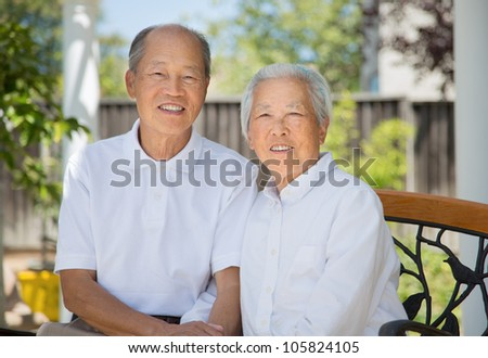 Happy Smiling Chinese Elderly Sitting on Garden Chair Backyard
