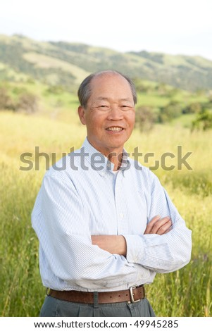 Happy Smiling Chinese Elderly Standing in front of Farmland