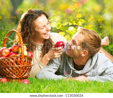 Happy Smiling Couple Having Fun on the Grass and Eating Apples in Autumn Garden.Healthy Food.Outdoor.Park.Basket of Apples.Harvest concept. Diet - stock photo
