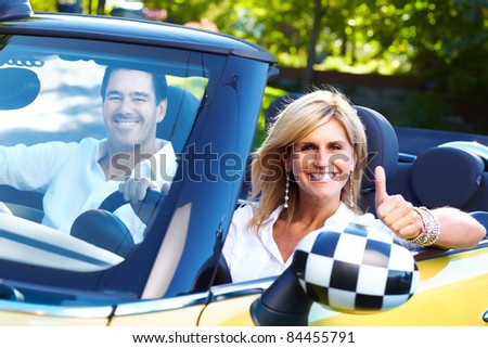 Happy smiling couple in a convertible car. People outdoors. - stock photo