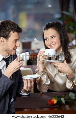 Happy smiling couple in cafe with cups in hands