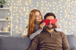 Happy smiling couple in love celebrating their relationship anniversary at home. Young people having fun on Saint Valentine's Day. Woman covering boyfriend's eyes with two red heart-shaped cards