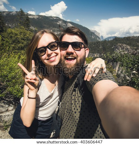 Happy smiling couple in love take selfie portrait while hiking in Yosemite National Park, California, USA.