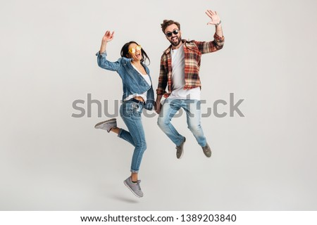 happy smiling couple isolated active jumping on white studio background, stylish mand and woman in casual denim hipster outfit wearing shirt and sunglasses having fun together, dating friends