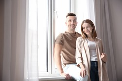 Happy smiling couple near plastic window