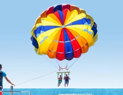 Happy smiling couple Parasailing on Tropical Beach in summer. Newlyweds under parachute hanging mid air. Having fun. Tropical Paradise. Positive human emotions.