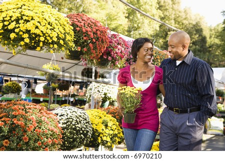 Happy smiling couple picking out flowers at outdoor plant market walking and holding hands.