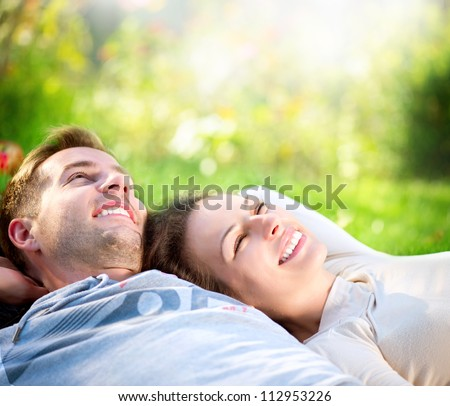 Happy Smiling Couple Relaxing on Green Grass.Park.Young Couple Lying on Grass Outdoor - stock photo