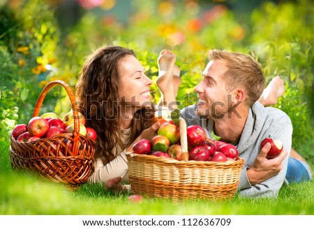 Happy Smiling Couple Relaxing on the Grass and Eating Apples in Autumn Garden.Healthy Food.Outdoor.Park.Basket of Apples.Harvest concept